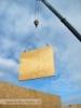 stěny dřevostavby jsou z kamionu na desku vykládány pomocí jeřábu (výstavba Hradec Králové, Stěžírky)
